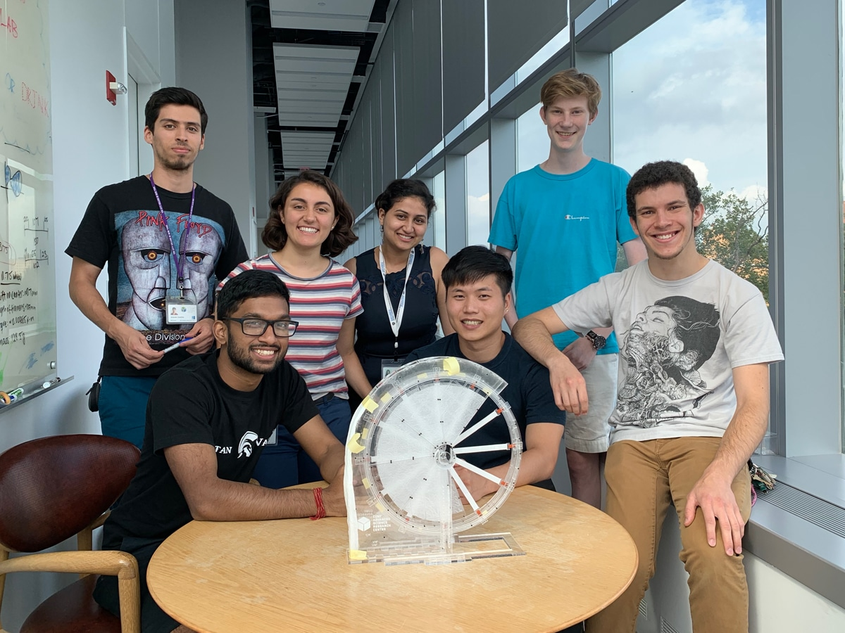 students post with an evaporation wheel inside the ASRC