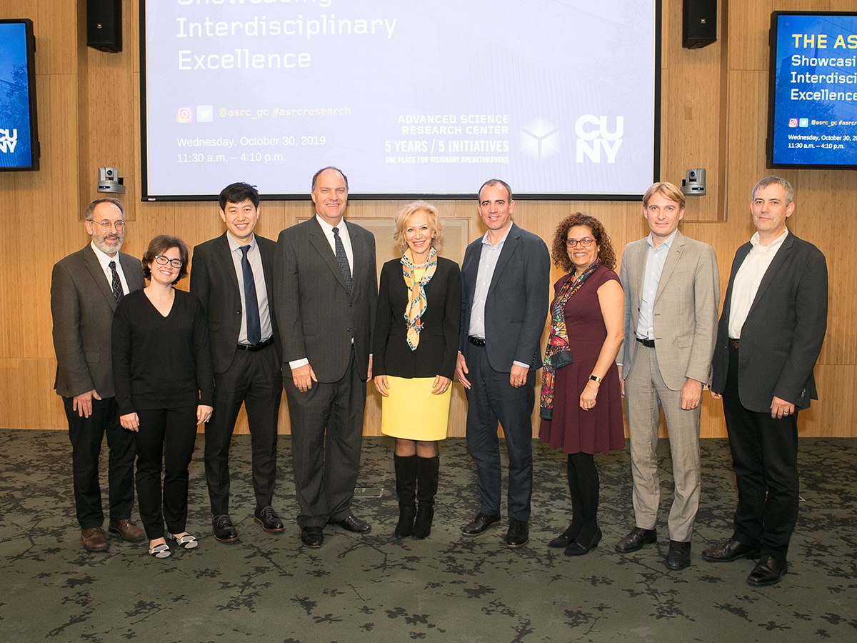 ASRC Initiative Directors, leaders, and CUNY faculty lstanding in front of presentation screen in the ASRC auditorium