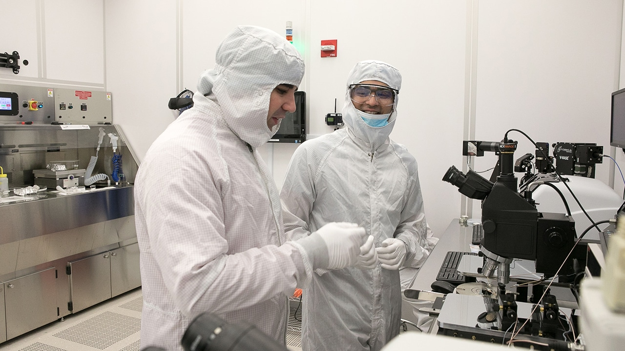 two scientists in full protective clean suits working at a microscope