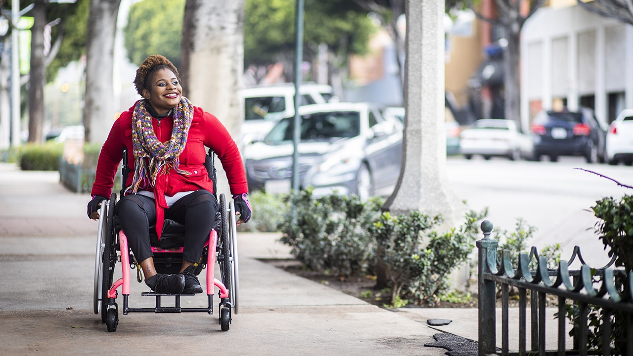 smiling Black woman in a wheelchair, on a sidewalk in a landscaped downtown area