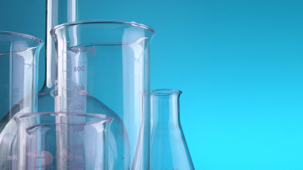 glass beakers and flasks against a blue background