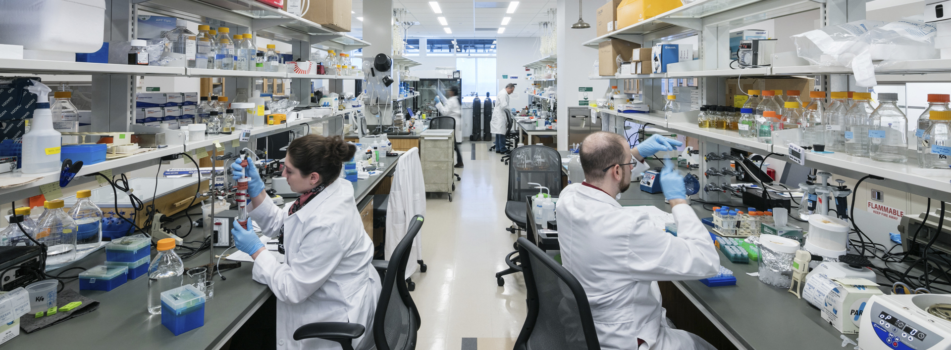 researchers in lab coats and gloves working in a lab