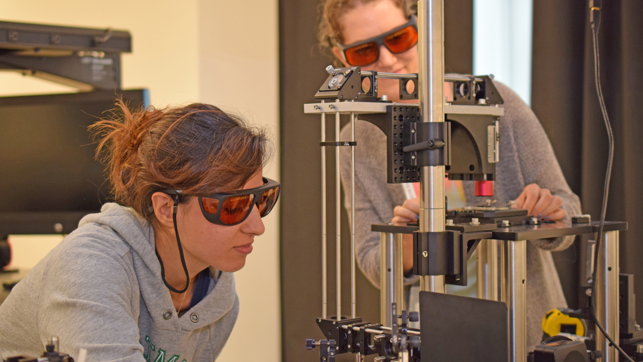two students wearing safety goggles and working with nanoscience equipment