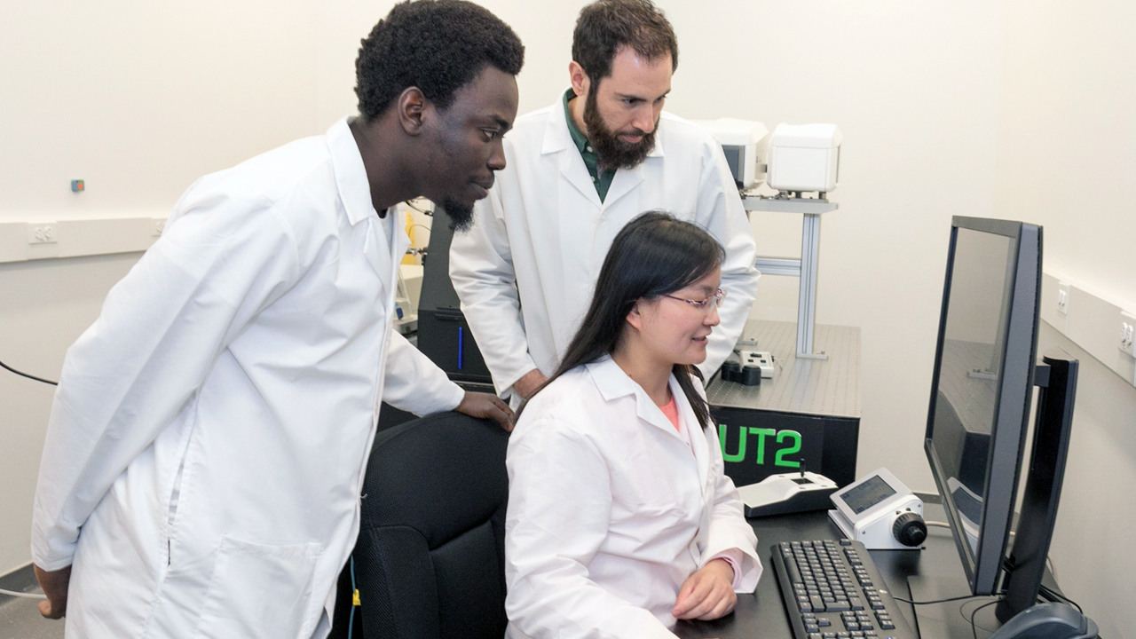 diverse group of neuroscience researchers looking at a computer screen