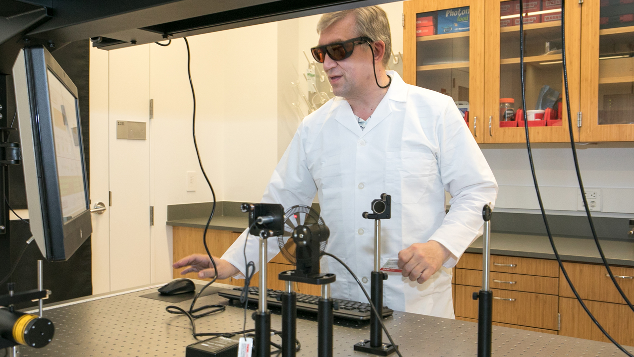 researcher in a lab coat working with laser equipment